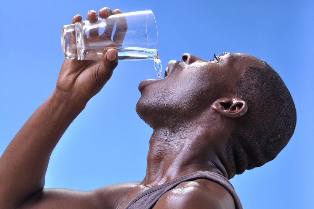 man drinking water because he's dehydrated